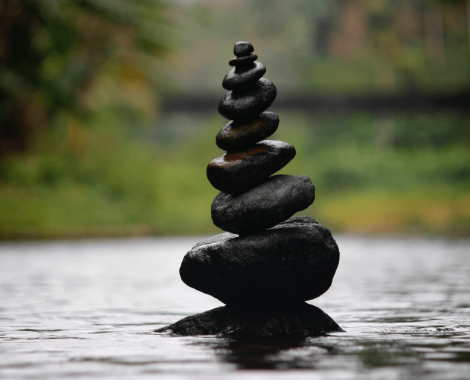 Dark stones are stacked in river